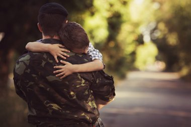 Boy and soldier in a military uniform say goodbye before a separation stock vector