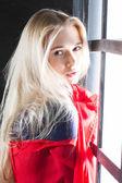 Mladá blondýnka s červeným šátkem v okně