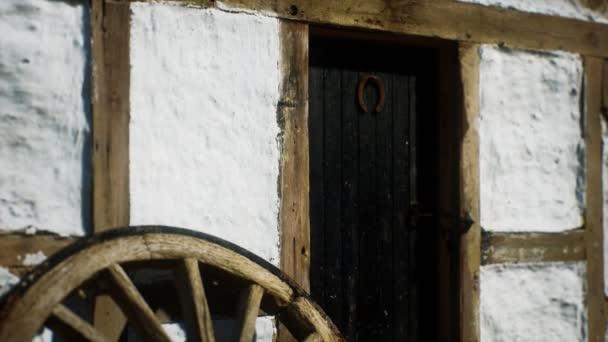 staré dřevěné kolo a černé dveře v bílém domě