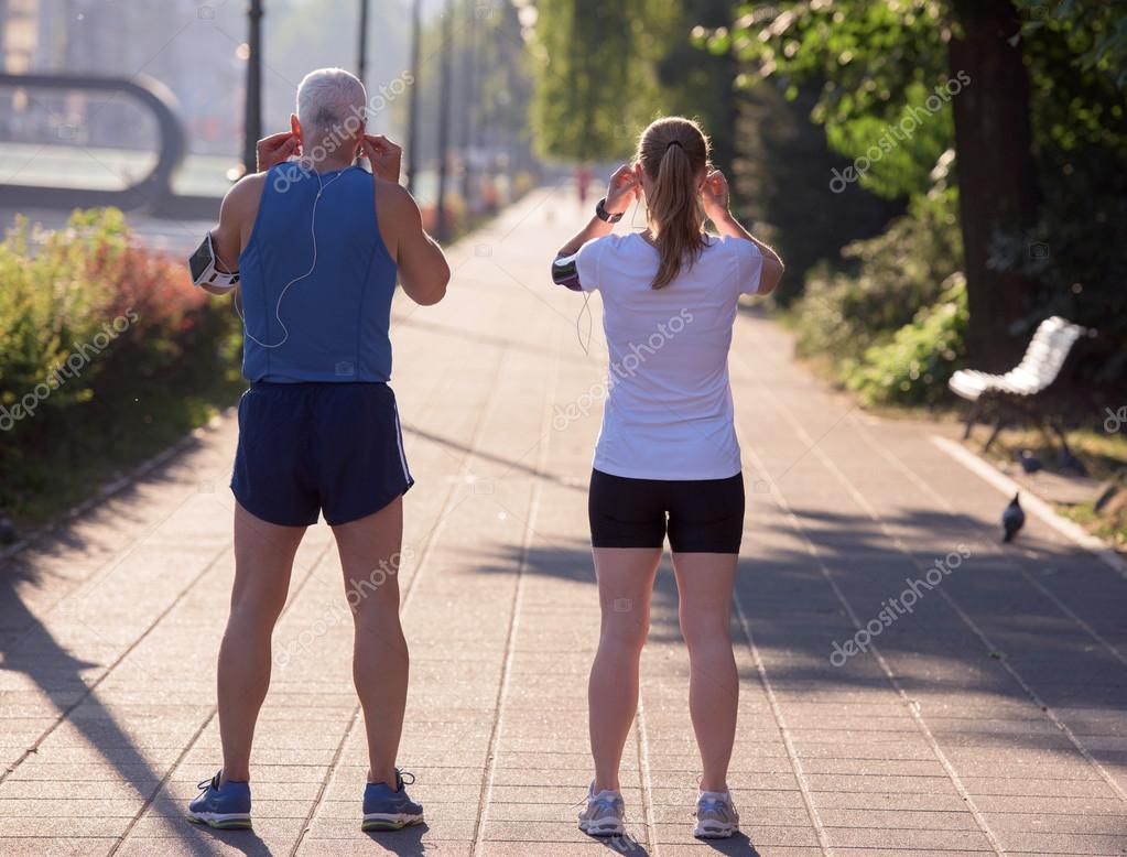 jogging couple planning running route and setting music — stock