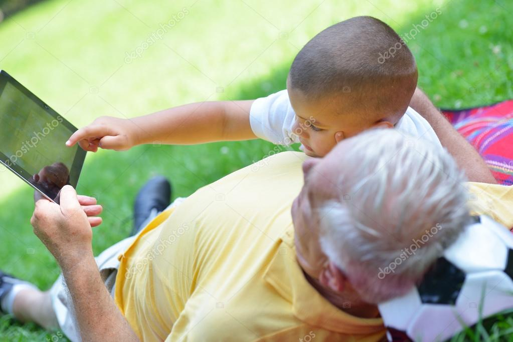 grandfather and child in park using tablet