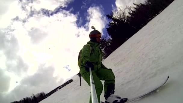 Lyžař jede z kopce s kamerou na helmě a v ruce