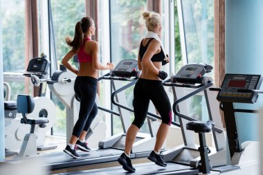 Friends exercising on a treadmill at gym