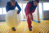Dělníci instalovat systém podlahového vytápění