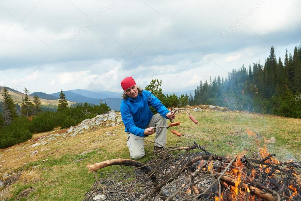 hiking man prepare tasty sausages on campfire