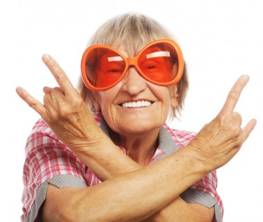 Senior woman wearing big sunglasses doing funky action isolated