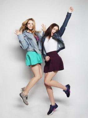 young hipster girls best friends jump