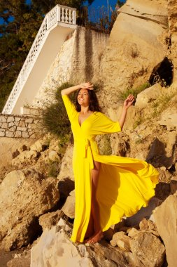 Woman with long yellow dress posing outdoor