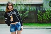 mladá žena jíst zmrzlinu slunečného dne venku