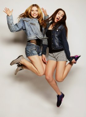 young hipster girls best friends jump