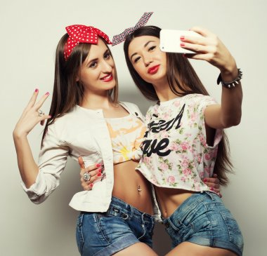 Two young funny women taking selfie with mobile phone stock vector