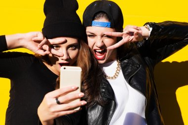 teenage girls friends outdoors make selfie on a phone.