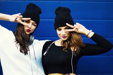 Two young hipster girl friends together having fun.