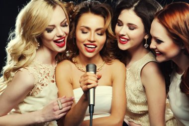 Four beautiful stylish girls singing karaoke