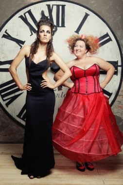Two Queens posing next to the clock.