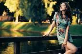 Módní bruneta žena pózuje na mostě