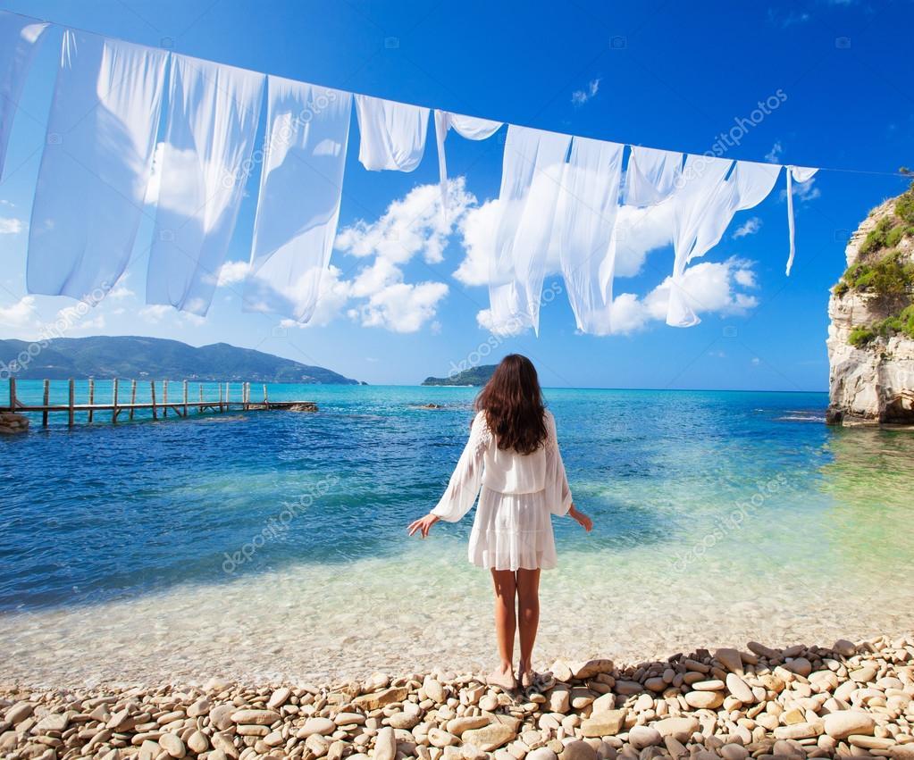e3b865412f4e Giovane donna del brunette in vestito da estate bianco in piedi sulla  spiaggia e sul mare. Ragazza caucasica
