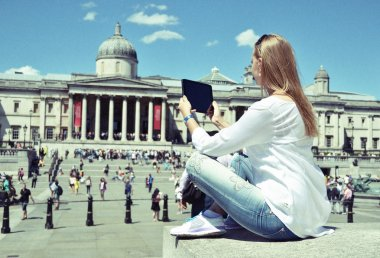 Girl with a tablet on Trafalgar square in London