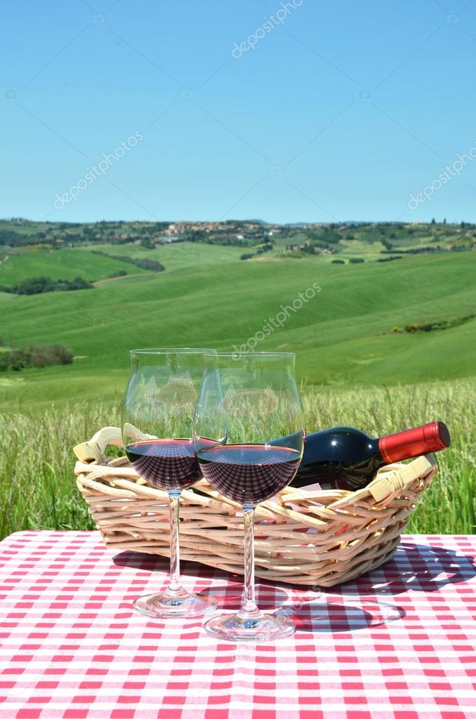 Red wine  against Tuscan landscape.