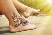 Fotografia Tatuaggio del hennè sul piede sulla spiaggia