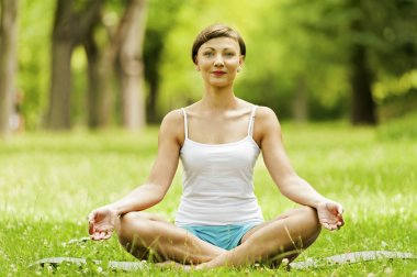 Yoga woman siting on grass relax.