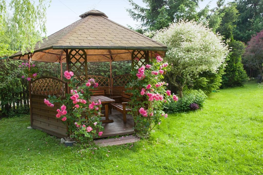 Kiosque de jardin en bois avec des roses et fond de paysage ...