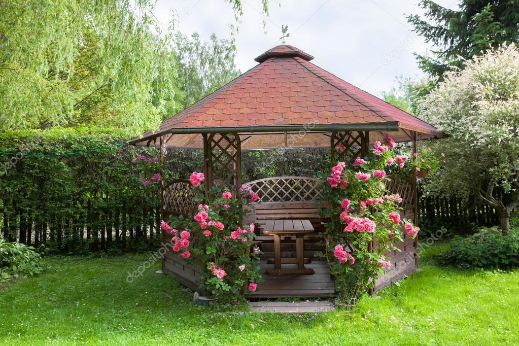 Kiosque de jardin en bois avec des roses et fond de paysage de l\'été ...