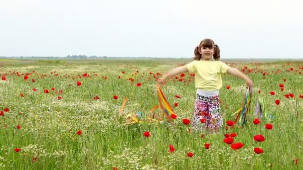 šťastná holčička mává s barevnými stuhami na louce
