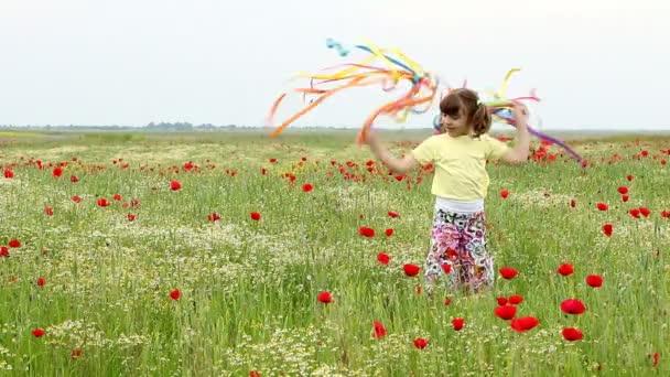holčička mává s barevnými stuhami na louce