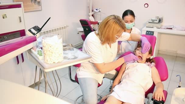 Zahnarzthelferin und kleine Patientin