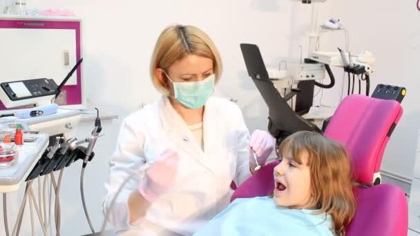 Weibliche Zahnarzt mit Bohrmaschine und kleine Mädchen