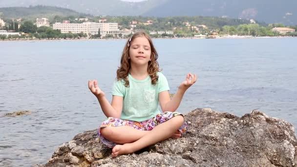 kislány ül egy szikla a tengerparton, és meditál