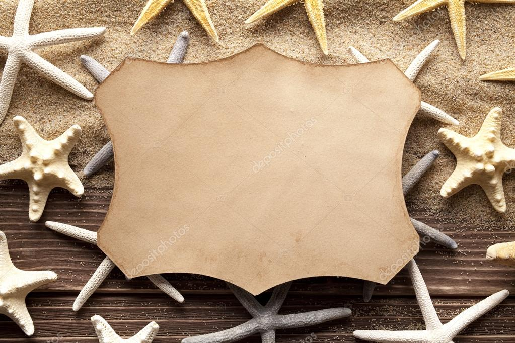 Blank paper label and starfishes on sand and wooden planks