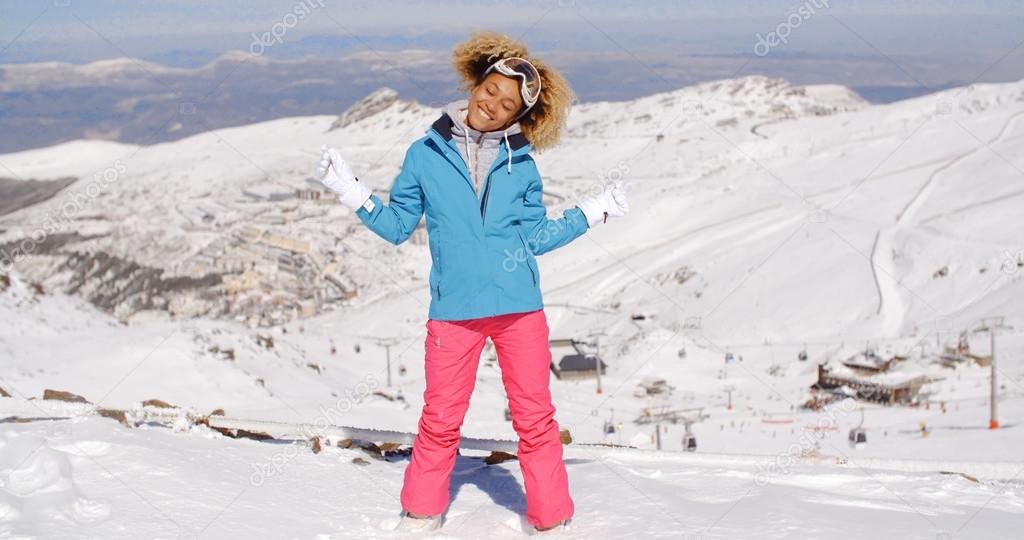 7e11cf835d Happy beautiful young adult woman in pink and blue skiing outfit waving  arms around in the air near top of hill with mountain in background — Photo  by ...