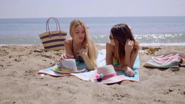women lying sun tanning on beach