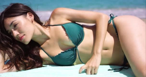 d4fdbc4aa30a Mujer acostada para tomar el sol en bikini sobre una toalla