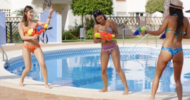 women playing with colorful water guns