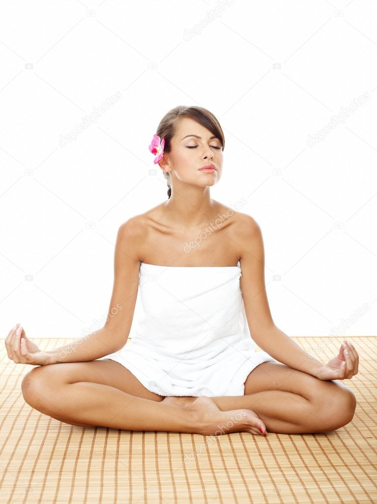 Woman doing lotus yoga pose stock photo dashek 58854673 pretty slim woman wrapped in white towel with purple flower on her ear doing lotus yoga pose on the floor at the spa captured with white background mightylinksfo