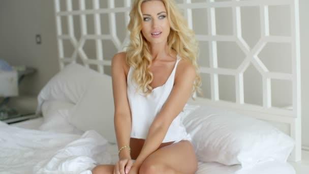 Sexy žena leží na posteli s koleno na koleno