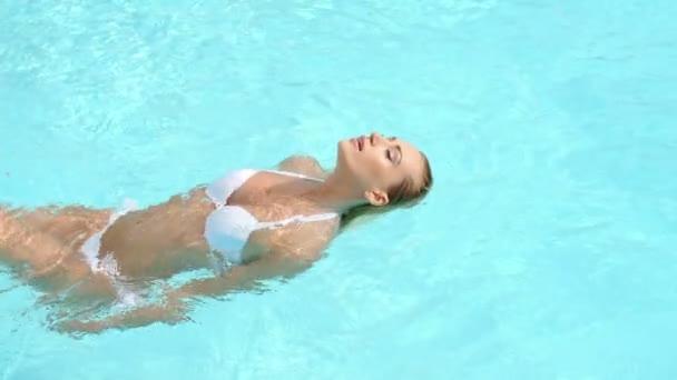 Žena plavání na zádech v bazénu