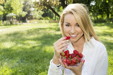 A beautiful young girl with strawberries outdoor