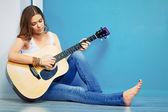 Fotografie Woman playing guitar