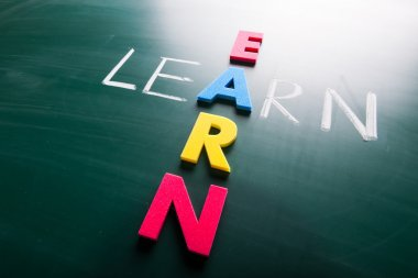 Learn and earn, conceptual words on blackboard.