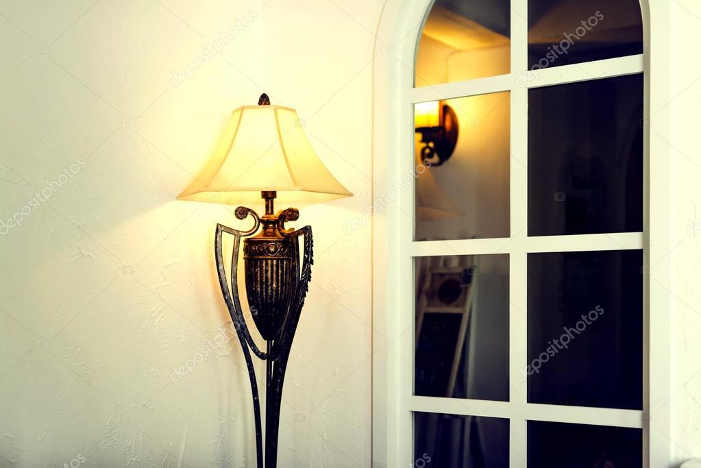 Antieke koperen vloerlamp naast wit muur en grille venster