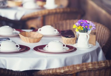 Table set for dinner in a restaurant or bistro with dinnerware a