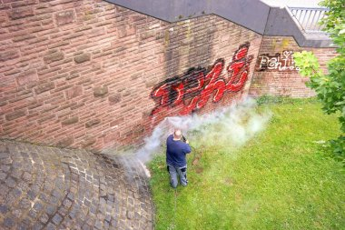 A worker washes a wall