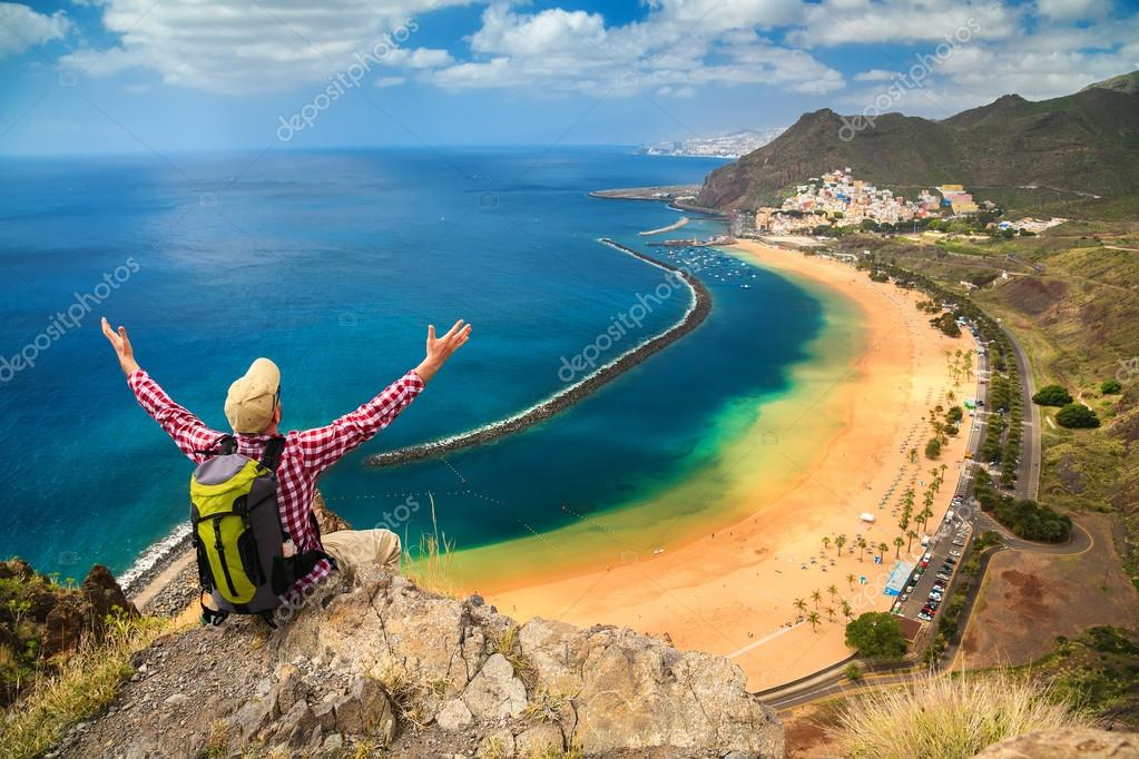man sitting on the edge of a cliff, enjoying view of Playa de La