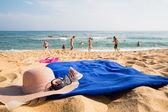 Fotografie Klobouk, ručník, sluneční brýle a pantofle na tropické pláži