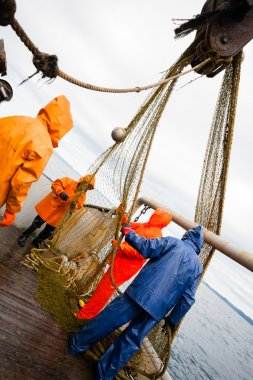 Fishermen in waterproof suits on the deck of the fishing vessel
