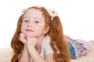 Little red haired girl lying